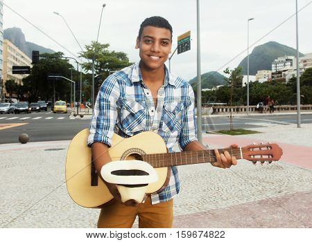 Street musician with guitar singing for cash outdoor in the city in the summer