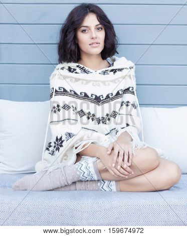 Beautiful natural young brunette woman wearing knitted poncho and socks sitting on a couch