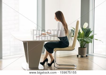 Side view portrait of young woman in a formal wear working at the modern office desk, competent secretary, office etiquette, professional opportunities and rights for women, small office environment