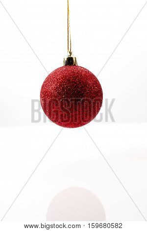 Red Christmas ball hanging in midair against a white background casting a reflection