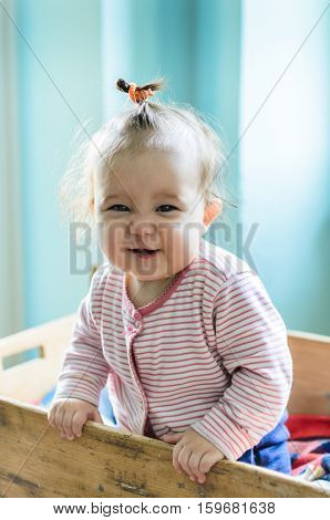 Close-up portrait of cute little baby girl with brunette hair in striped long sleeved bodysuit staying in old-fashioned rustic baby cot and smiling at camera with smart and curious beautiful hazel brown eyes