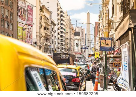 BUENOS AIRES ARGENTINA - NOVEMBER 17 2016: yellow taxi cab in rush hour and traffic jam congestion on Avenida Corrientes in downtown area in argentinian capital city - Warm afternoon color tones