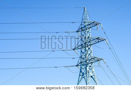 High voltage metal power pole with wires tangle on blue sky background
