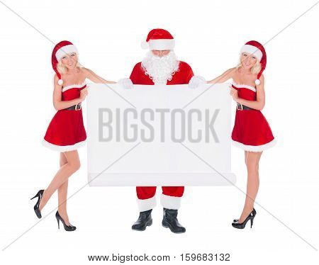 Santa Claus and two happy blonde cute Snow Maiden women with empty christmas white paper scroll advertising poster isolated on white background