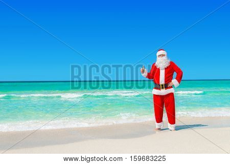 Santa Claus at tropical beach with pleasure thumbs up gesture by hand Christmas or New Year's vacation in hot countries concept