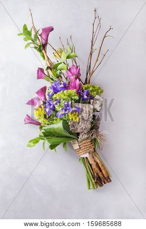 Creative сolorful bouquet of iris and orchid and wooden branches. Still life with colorful flowers. Fresh flowers. Place for text. Flower concept. Fresh spring bouquet. Summer Background