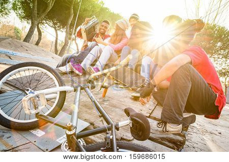 Group of trendy friends having fun together at skate bmx park - Youth friendship concept with young people outdoors - Focus on afroamerican guy with stereo - Retro vibrant filter with sunflare halo