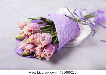 Bouquet of lilac tulips wrapped in lilac paper. Still life with colorful tulips. Fresh spring tulips. Place for text. Flower concept. Fresh spring bouquet. Summer Background