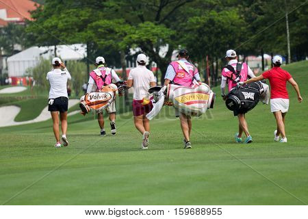 KUALA LUMPUR, MALAYSIA - OCTOBER 29, 2016: LPGA golfers walk towards the green from the fairway at the TPC Golf Course at the 2016 Sime Darby LPGA Malaysia golf tournament.