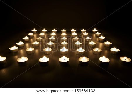Rows of votive candles burning in the darkness in a church in a spiritual background for Christian beliefs a vigil or in remembrance of a loved one