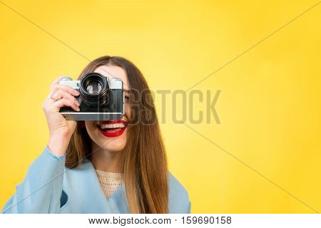 Stylish woman photographer with retro camera on the yellow wall background. Image with copy space