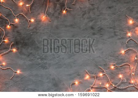 Christmas lights frame on dark grey stone background with snow, copyspace