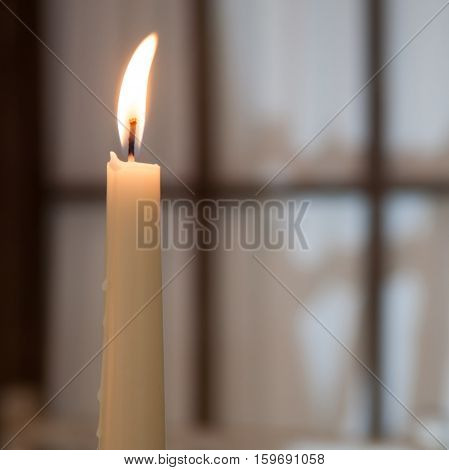 White high burning candle in the evening in the room against the window. Concept: the comfort of home warmth comfort tranquility copy space.