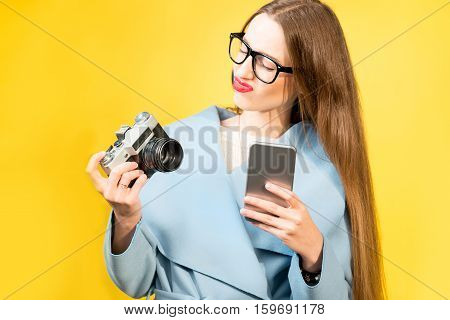 Confused nerdy woman photographer with retro camera and phone on the yellow wall background