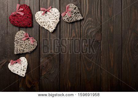 Concept of Valentine's Day. Wicker hearts on dark wooden background.