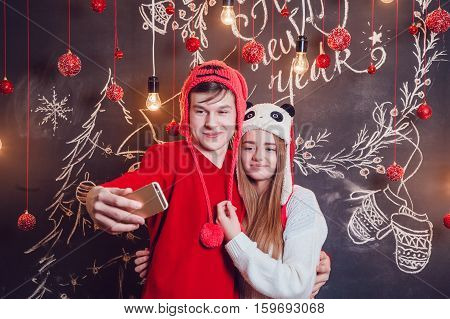 Happy couple standing hugging on a dark background with Christmas pattern. New year.