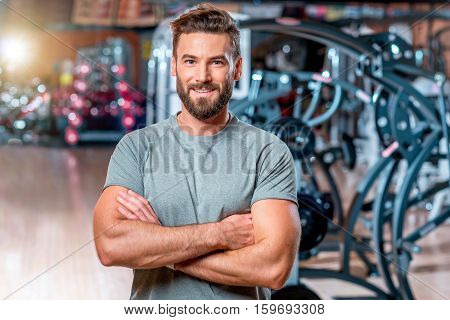 Lifestyle portrait of handsome muscular man standing in the sport gym
