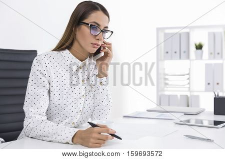 Bespectacled woman with brown hair is talking on the phone holding a pen and looking concerned. Concept of communication