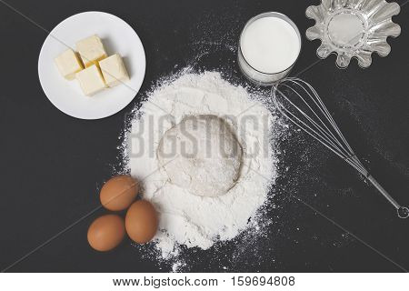 Top view of dough flour eggs milk and butter lying on a black table with a cake making form