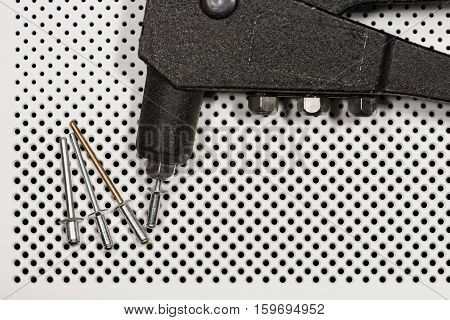 Detail of an old rivet gun (hand riveter) with rivets on a white background with holes
