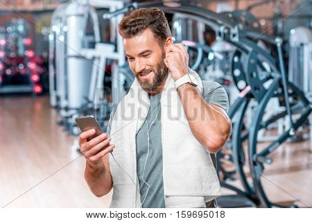 Lifestyle portrait of handsome smiling man standing with mobile phone after the training in the sport gym