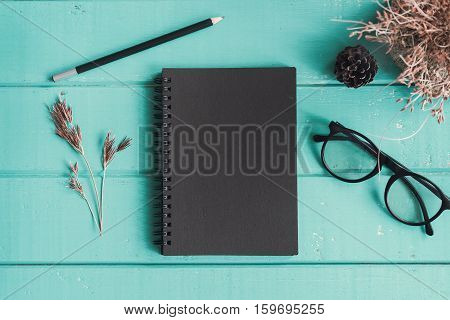 Dry flower with blank notebook on old wooden table Vintage tone