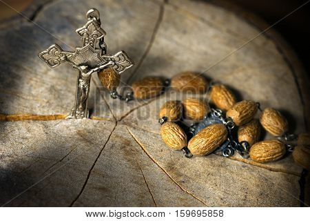 Detail of a silver crucifix and a rosary with wooden beads. On a tree trunk section