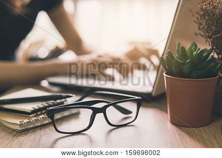 Businesswoman typing on laptop at workplace in home office. Vintage tone