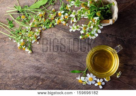 cup of chamomile tea with chamomile flowers on wooden planks with copy space.