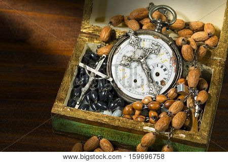 Time to pray - Open wooden box full of rosary beads crucifixes and an old pocket watch with a vintage silver crucifix