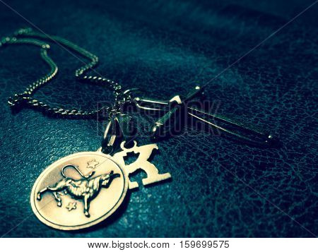 A necklace with three pendants: a letter k a cross and the bull zodiac sign