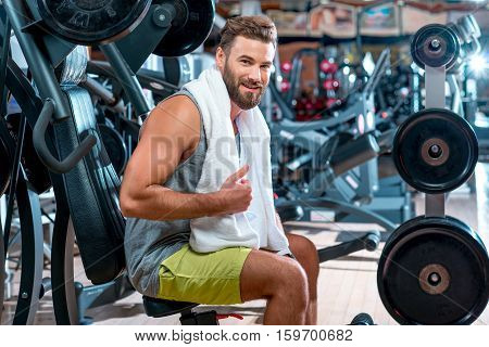Lifestyle portrait of handsome muscular man with towel sitting on the simulator in the gym