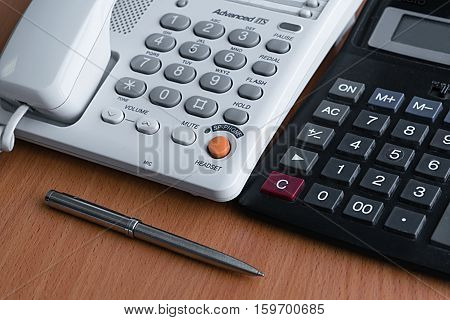 telephone calculator and metal ballpoint pen lying on a light wooden table in the office at work preparing for the working day and making cold calls to clients