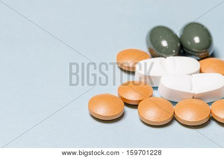 group of pills over a pale blue background with copys space on the left. pharmaceutical. disease. cure. medicine