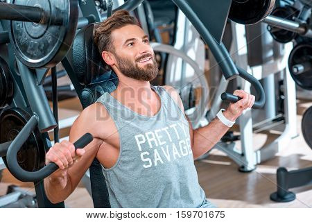 Muscular man training with simulator in the gym