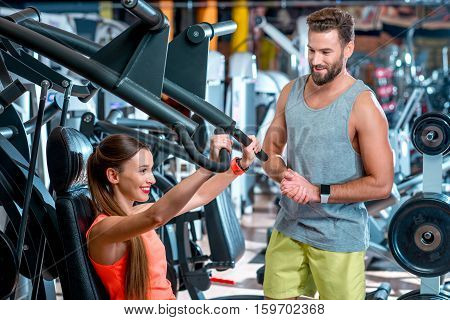 Young woman with personal trainer exercising on the simulator in the gym. Sport couple training together