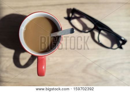 Cup of coffee and glasses with shadow on wooden desk Top view