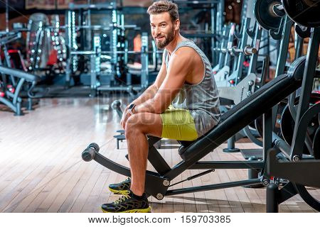 Lifestyle portrait of handsome muscular man sitting on the simulator in the gym