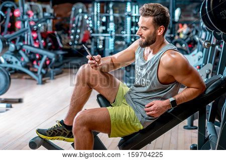 Lifestyle portrait of handsome muscular man with phone sitting on the simulator in the gym