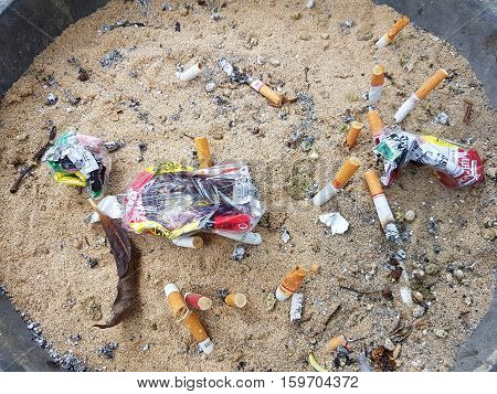 CHIANG RAI THAILAND - NOVEMBER 25: Used cigarette butt in dirty ash tray with sand and crumpled cigarette case on November 25 2016 in Chiang rai Thailand
