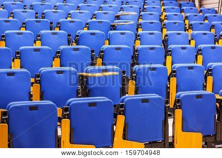 This is closeup of rows of blue seats in lecture hall.