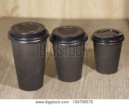 three paper Cup of black coffee on wooden background