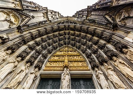 The main archway to the entrance to Cologne cathedral taken looking straight up with Mary at the center.