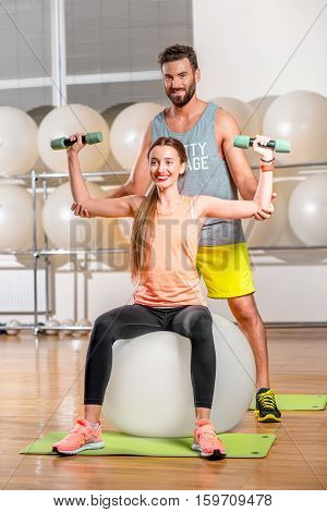 Young woman lifting dumbbells with personal trainer in the fitness room with fitballs on the background