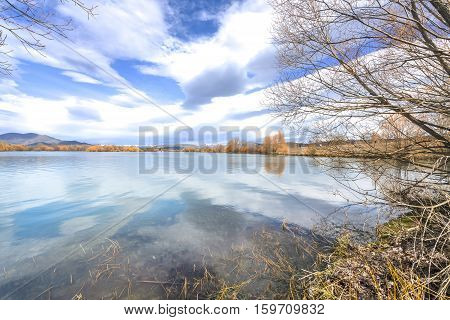 Lake water reflection with lenticular cloud skies
