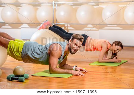 Sports couple making exercise with fitballs in the fitness room
