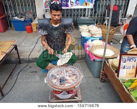 KANCHANABURI THAILAND - NOVEMBER 26: unidentified man in Thai ancient warrior suit making Giant Rice Crispy at Pakphraek market walking street on November 26 2016 in Kanchanaburi Thailand