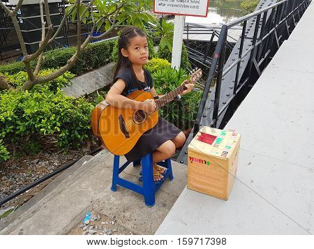 KANCHANABURI THAILAND - NOVEMBER 26: unidentified asian girl playing guitar for donating on Bridge on the river Kwai on November 26 2016 in Kanchanaburi Thailand