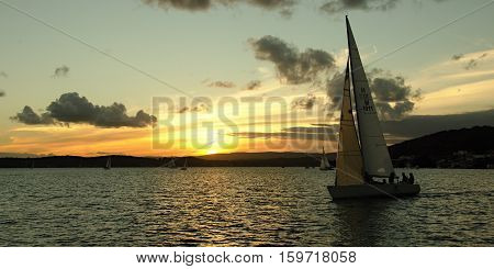 Sunset finish to twilight sailing event Lake Macquarie Sailing Club New South Wales Australia.
