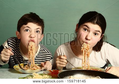 happy teen siblings boy and girl eat spaghetti together hanging from mouth grimacing happily